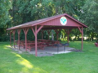 A red wooden pavilion with picnic tables inside.