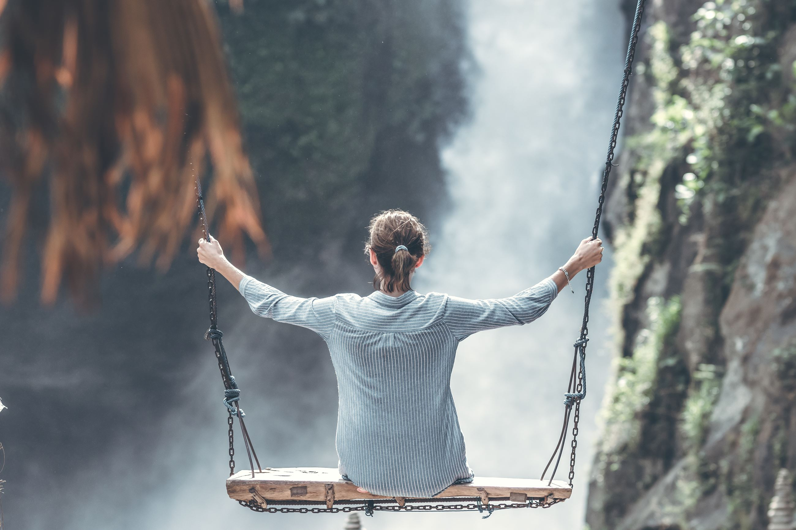 Canva - Woman Riding Big Swing in Front of Waterfalls (1)