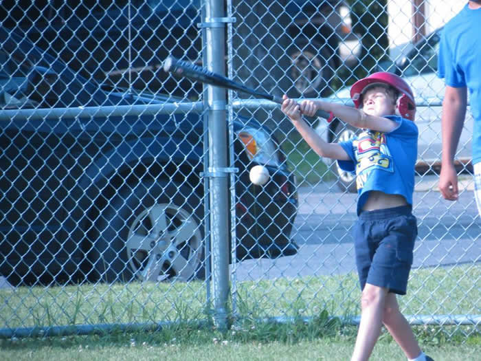 A small boy swinging his bat at a ball.