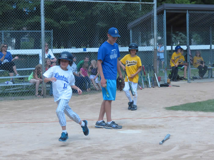 A young boy running towards first base.