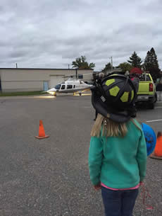A young girl in a firefighter helmet looking at a helicopter.
