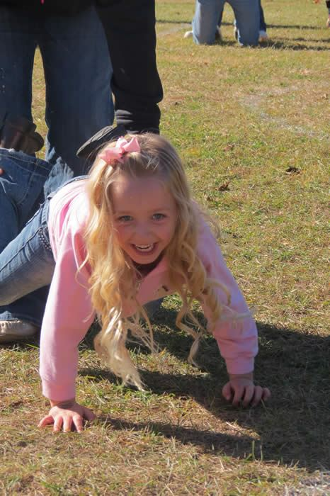 A young girl participating in a wheelbarrow race.